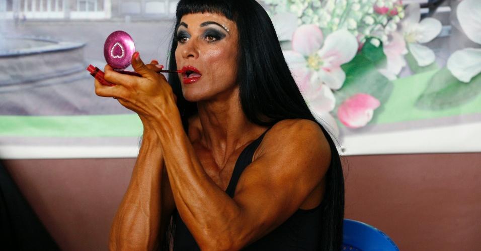 06.out.2013 - Atleta faz últimos retoques em maquiagem antes de participar de competição de fisiculturismo, em Krasnoyarsk, na Rússia