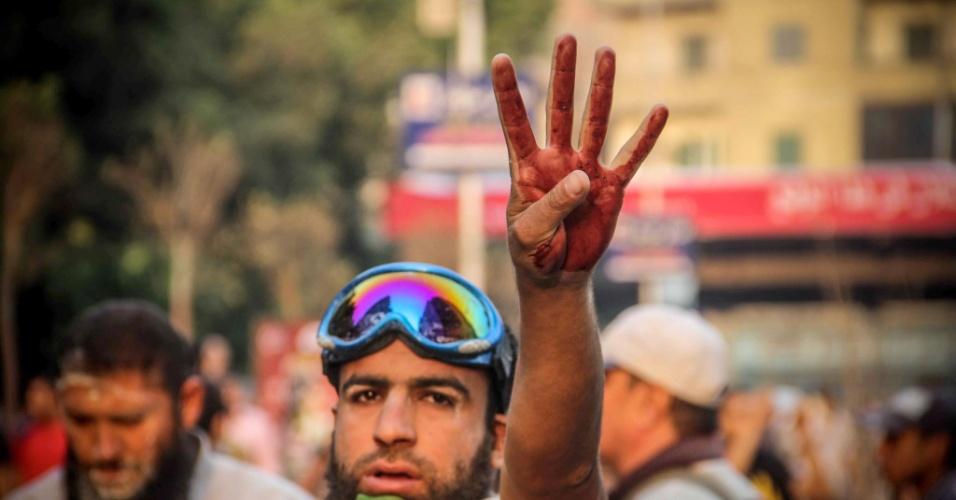 6.out.2013 - Simpatizante de Mohammed Morsi, presidente deposto do Egito, mostra as mãos sujas de sangue em sinal aos 40 anos da guerra árabe-israelense de 1973. Confrontos entre partidários, opositores e forças de segurança deixaram ao menos 38 pessoas mortas no país