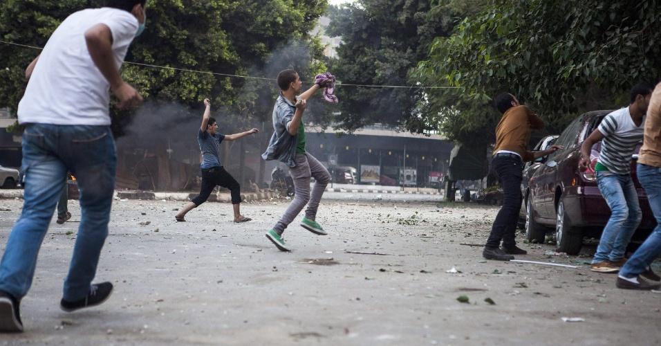 6.out.2013 - Simpatizantes de Mohammed Morsi, presidente deposto do Egito, jogam pedras em confronto com  opositores e forças de segurança nas ruas do Cairo. Conflito deixou ao menos 38 pessoas mortas no dia em que o país comemora o 40º aniversário da guerra árabe-israelense de 1973