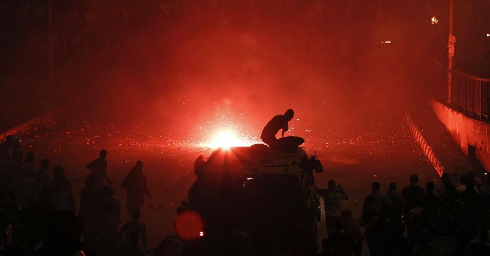 6.out.2013 - Um oficial da tropa de choque da polícia do Egito sobe em um veículo blindado para disparar balas de borracha contra os membros da Irmandade Muçulmana e apoiadores do presidente deposto Mohamed Mursi em rua próxima à praça Ramsis, no Cairo, que leva à famosa praça Tahrir. Os confrontos entre partidários, opositores e forças de segurança deixaram ao menos 38 pessoas mortas no dia em que o país comemora o 40º aniversário da guerra árabe-israelense de 1973