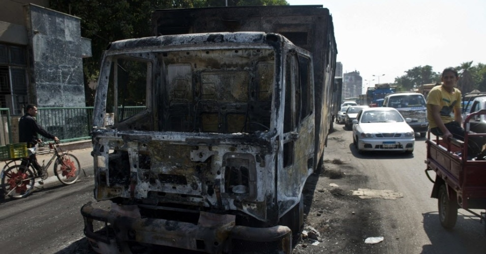 7.out.2013 - Egípcios passam por um carro da polícia queimado no Cairo, que foi incendiado por membros da Irmandade Muçulmana na noite anterior, durante confrontos com a polícia. Os confrontos eclodiram após partidários e opositores do presidente deposto do Egito, Mohamed Morsi, convocaram atos para marcar o aniversário da guerra de 1973 entre árabes e israelenses