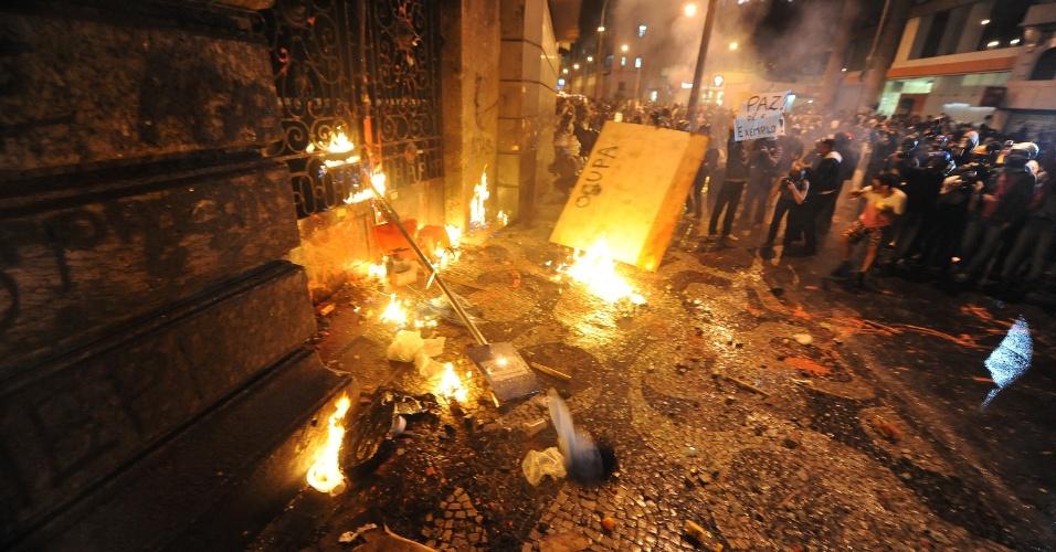 7.out.2013 - Manifestantes incendeiam com bombas caseiras a porta lateral da Câmara de Vereadores do Rio de Janeiro, durante protesto de professores na Cinelândia, região central da cidade