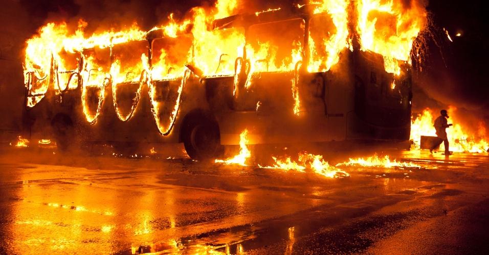 7.out.2013 - Manifestantes mascarados incendeiam um ônibus durante protesto de professores na Cinelândia, região central do Rio de Janeiro