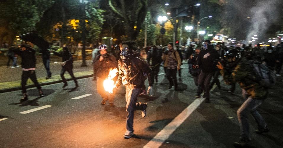 7.out.2013 - Um grupo de Black Blocs colocou fogo em sacos de lixo durante um protesto nas proximidades da praça da República, no centro de São Paulo, na noite desta segunda-feira (7).  Manifestantes responderam jogando pedras contra uma barreira de policiais