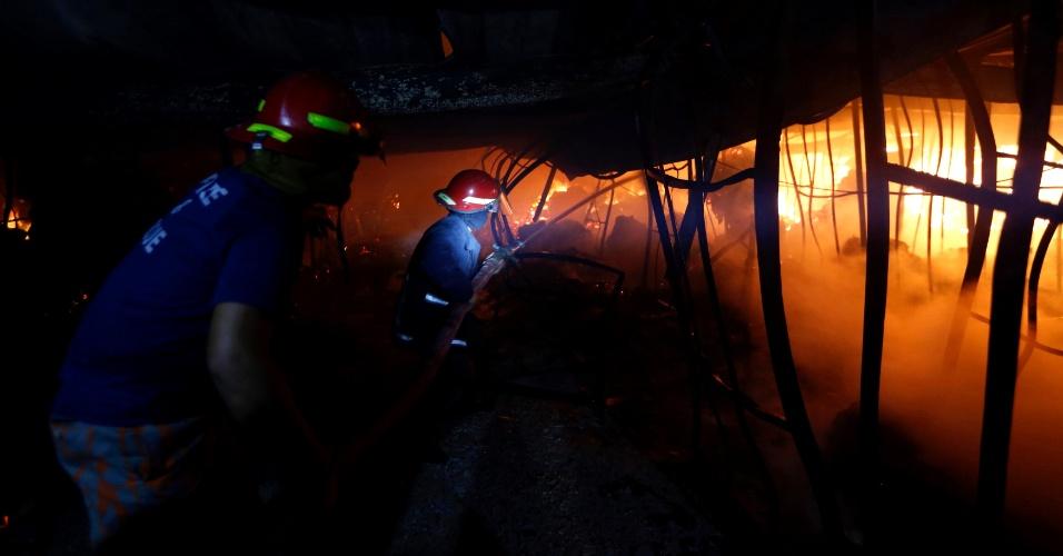 9.out.2013 - Bombeiros tentam controlar incêndio no interior de fábrica têxtil na cidade de Gazipur (Bangladesh). Nove funcionários, incluindo três gestores da empresa, morreram no incêndio que se originou na seção dos teares da fábrica Aswad Composite Mills. Cerca de 50 trabalhadores ficaram feridos