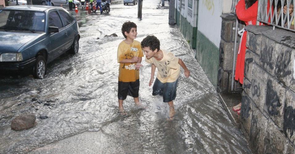 9.out.2013 - Crianças brincam em rua inundada de Vila Isabel, na zona norte do Rio de Janeiro, após o rompimento de uma adutora na região. Ao menos cinco ruas do bairro ficaram alagadas