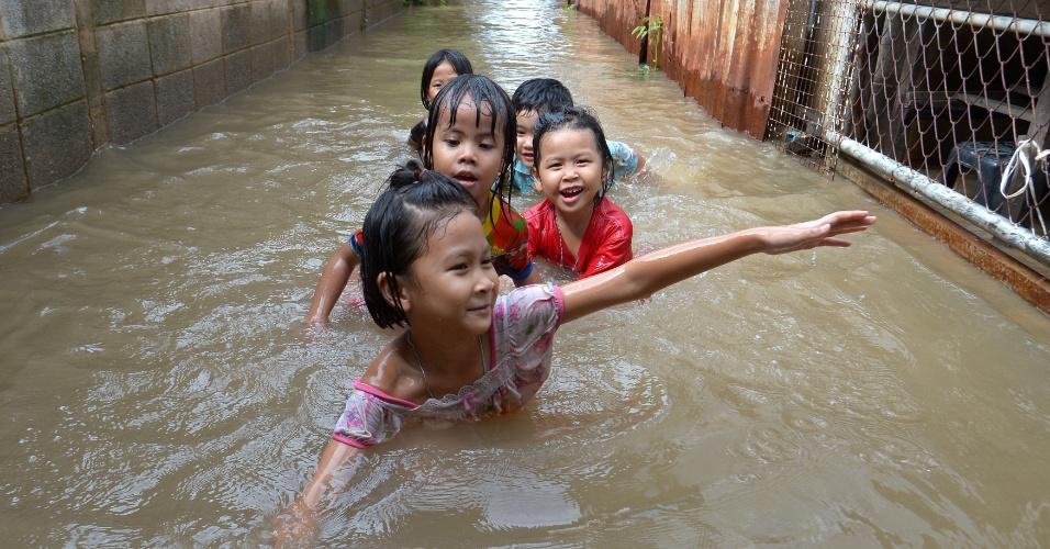 9.out.2013 - Crianças tailandesas brincam em enchente em um templo budista na província de Pathum Thani, ao norte de Bancoc.  O Departamento de Prevenção e Mitigação de Desastres informou que 27 províncias da Tailândia ainda estão alagadas e 31 pessoas já morreram devido às inundações