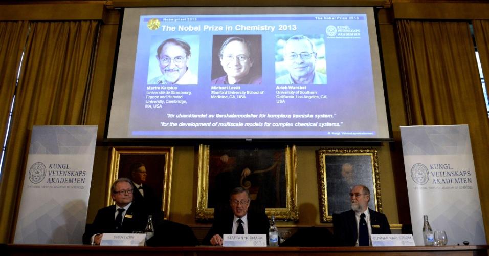 9.out.2013 - Da direita para a esquerda, Sven Lidin, Staffan Normark e Gunnar Karlstrom se sentam diante de tela onde são mostrados os cientistas Martin Karplus, Michael Levitt e Arieh Warshel, durante entrevista coletiva de anúncio dos ganhadores do Nobel de Química de 2013, em Estocolmo (Suécia). Os três recebem o prêmio por desenvolverem modelos de múltiplas escalas para sistemas químicos complexos