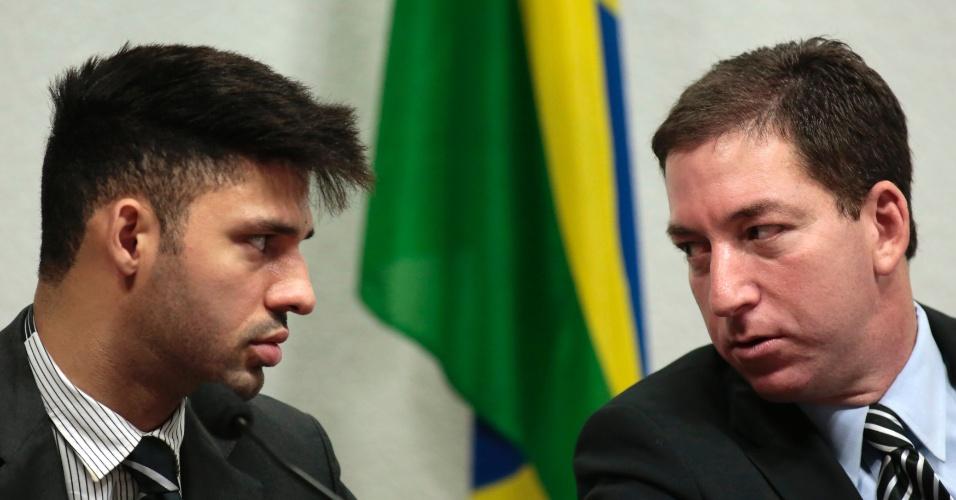 9.out.2013 - Glenn Greenwald (direita), jornalista norte-americano que publicou os documentos vazados por Edward Snowden, olha para o parceiro David Miranda durante depoimento na Comissão Parlamentar de Inquérito do Senado Federal, em Brasília. A CPI foi criada para investigar as  denúncias de espionagem dos Estados Unidos no Brasil