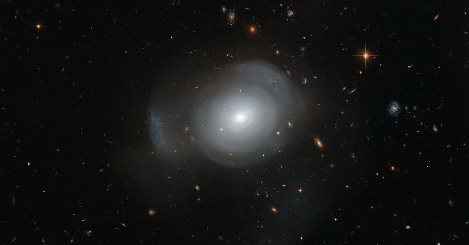 """10.out.2013 - A galáxia elíptica PGC 6240 se assemelha a uma """"pálida rosa cósmica"""" no novo registro do telescópio Hubble. Localizada na constelação de Hydra, a 350 milhões de anos-luz de distância da Terra, a galáxia surgiu de uma recente fusão, já que abriga tanto estrelas jovens e quentes quanto mais velhas"""