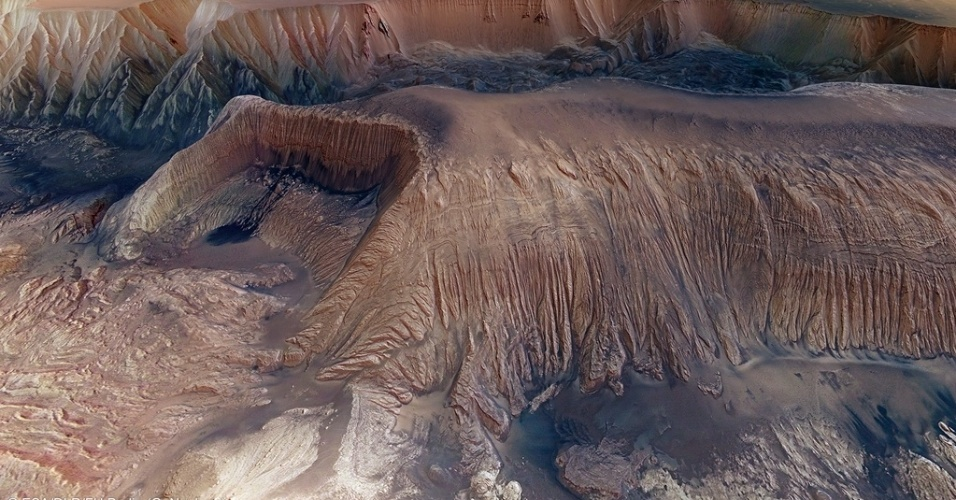 10.out.2013- A grande depressão chamada Hebes Chasma em Marte, ao lado dos cânions Valles Marineris, tem quase 8 km de profundidade e 315 km de largura de leste a oeste e 125 km de norte a sul, e é vista nesta nova imagem que reúne outras oito em alta resolução em um mosaico da ESA (Agência Espacial Europeia). As origens do chasma estão ligadas ao vulcão Olympus Mons, na região de Tharsis