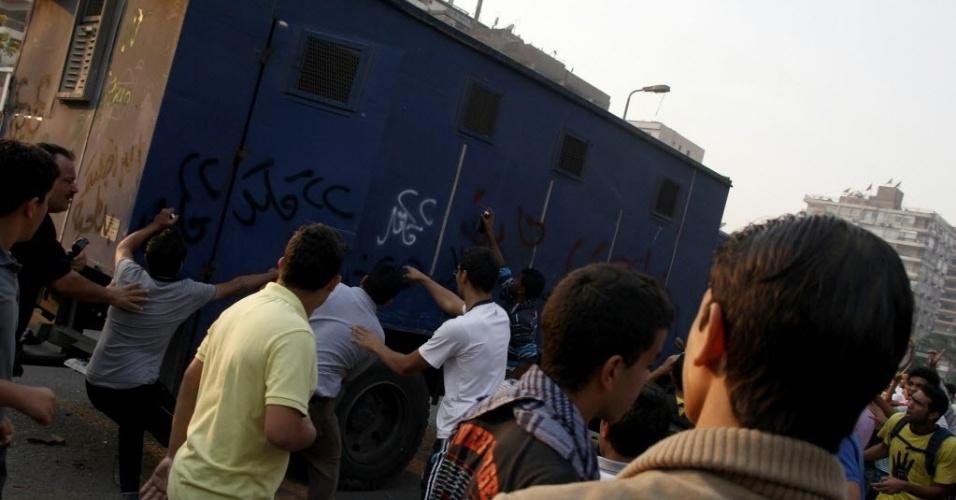 11.out.2013 - Apoiadores do presidente egípcio deposto, Mohammed Mursi, atacam um veículo da polícia durante protesto contra as forças armadas do país, em Nasr City, no leste do Cairo, nesta sexta-feira (11). Uma aliança islâmica instou seus apoiadores a ficarem longe da praça Tahrir, no Cairo, para evitar derramamento de sangue, após uma semana em que cerca de 80 egípcios foram mortos