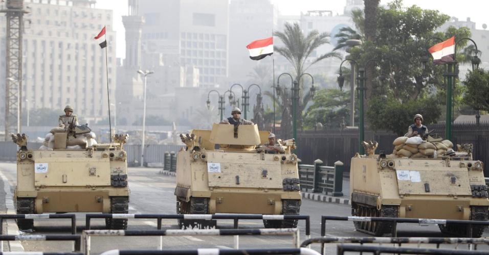 11.out.2013 - Soldados sentam no topo dos seus tanques enquanto passam pelos arredores da praça Tahrir, no Cairo, nesta sexta-feira (11). Milhares de apoiadores do presidente egípcio deposto, Mohammed Mursi, protestaram em Cairo, Alexandria e nas cidades do delta do rio Nilo, segundo fontes seguras