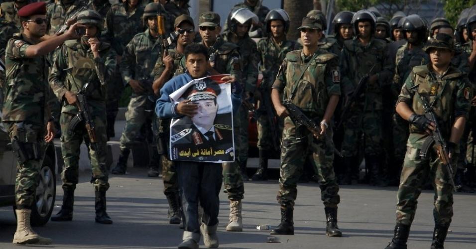11.out.2013 - Um homem segura um cartaz com a foto do general Abdel Fattah al-Sisi, sendo rodeado por soldados do Exército egípcio que montavam guarda no distrito de Nasr City, no leste do Cairo, nesta sexta-feira (11). Milhares de apoiadores do presidente egípcio deposto, Mohammed Mursi, protestaram em Cairo, Alexandria e nas cidades do delta do rio Nilo, segundo fontes seguras