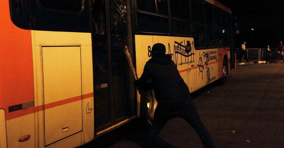 15.out.2013 - Integrante do Black Bloc quebra vidro de ônibus durante protesto contra a política educacional do governo de Geraldo Alckmin na capital paulista. A manifestação teve início no início da noite no largo da Batata, em Pinheiros. Manifestantes entraram em confronto com a polícia, que usou bombas de gás lacrimogêneo e efeito moral