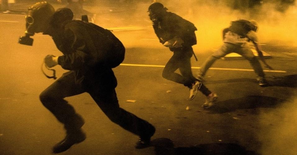 15.out.2013 - Manifestantes entram em confronto com a polícia após protesto de professores no Rio de Janeiro na noite desta terça-feira (15); ativistas usam máscaras contra os efeitos do gás lacrimogêneo