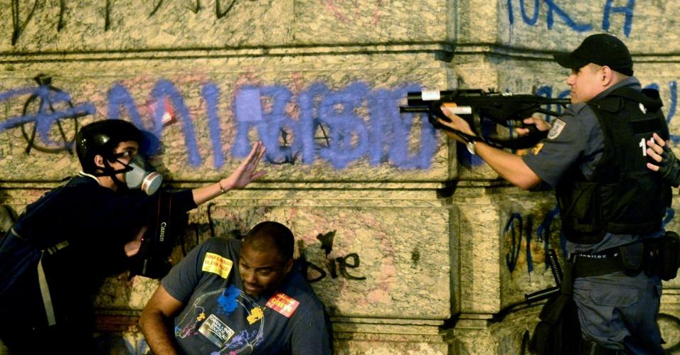 15.out.2013 - Policial aponta equipamento contra manifestante durante protesto na região central do Rio de Janeiro, nesta terça-feira (15), Dia do Professor