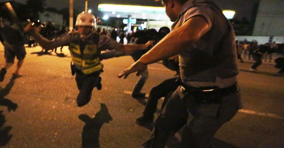 15.out.2013 - Policial militar cai ao ser chutado por manifestante durante profesto em São Paulo, nesta terça-feira (15), Dia do Professor
