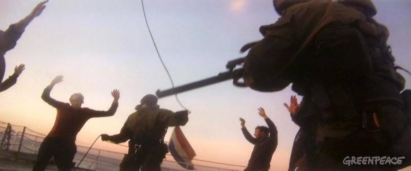 """15.out.2013 -Fotos de um celular mostram o momento em que a guarda costeira russa sobe ilegalmente e fortemente armada a bordo do Arctic Sunrise, navio do Greenpeace, segundo divulgou a ONG """"Eu peço para as pessoas verem essas fotos e decidirem se ativistas pacíficos, com os braços levantados e sob a mira de pistolas podem de algum modo serem chamados de piratas"""", disse Kumi Naidoo, diretor-executivo do Greenpeace Internacional"""