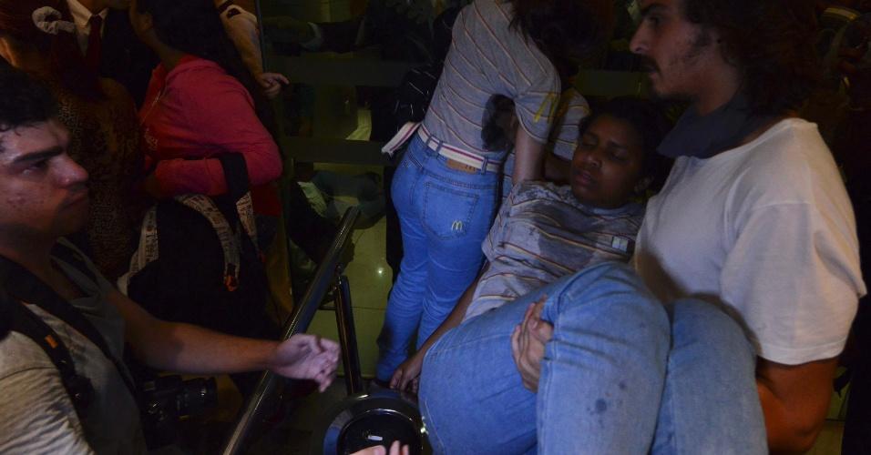 15.out.2013 - Funcionária de loja da McDonald's passa mal durante confronto entre policiais e integrantes do Black Blocs no centro do Rio de Janeiro, nesta terça-feira (16). Uma loja da rede foi depredada durante o ato, que aconteceu após o protesto dos professores