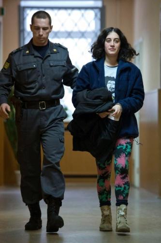 16.out.2013 - A turca Gizem Akhan, uma das 30 ativistas detidos do Greenpeace após um protesto no Ártico, é escoltada por policial no corredor da corte de Murmansk, na Rússia. Ela está entre os quatro estrangeiros que tiveram seu pedido de liberdade sob fiança negado pela justiça russa nesta quarta-feira