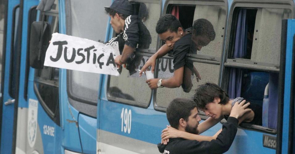 16.out.2013 - Homem abraça manifestante através da janela de ônibus da Polícia Militar, que leva os detidos na noite de terça-feira, durante confronto com policiais, do 25º DP, em Engenho Novo, zona norte do Rio, para o Instituto Médico Legal. Ao fundo, um dos detidos ergue cartaz com a palavra
