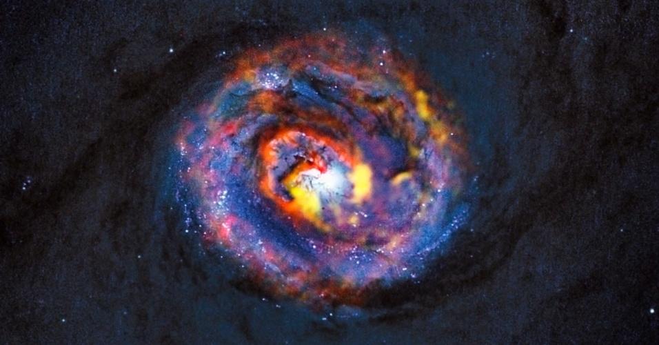 16.out.2013 - O tênue fundo azul representa as faixas centrais de poeira da galáxia NGC 1433, que foi obtida pelo telescópio espacial Hubble, operado em conjunto pelas Agências Espaciais Norte-Americana (Nasa) e Europeia (ESA). Já as estruturas coloridas, perto do centro, correspondem às novas observações feitas pelo ALMA, operado pelo Observatório Europeu do Sul (ESO, na sigla em inglês), que revelam pela primeira vez uma estrutura em espiral, assim como uma inesperada corrente de material que se desloca para fora