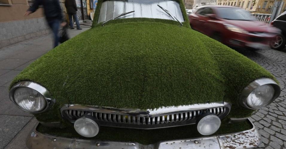 17.out.2013 - Carro antigo Volga modelo GAZ-21, da era soviética, coberto por grama artificial faz propaganda de uma loja de laticínios em uma rua de São Petersburgo, na Rússia