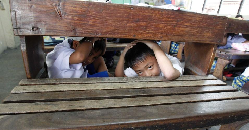 17.out.2013 - Estudantes se escondem em mesa nesta quinta-feira (17) em escola de Manila (Filipinas) durante exercício de prevenção de danos por terremoto. O número de mortos pelo tremor ocorrido no país na terça-feira (15) aumentou para 156 pessoas, de acordo com o governo. Cerca de 3 milhões de filipinos foram afetados