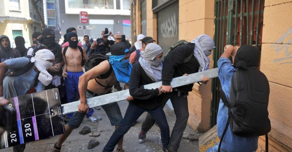 17.out.2013 - Estudantes tentam arrombar uma porta durante manifestação por melhorias no sistema público de educação chileno, em Santiago, nesta quinta-feira (17)