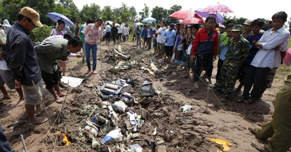 17.out.2013 - Moradores observam nesta quinta-feira (17) em Pakse (Laos) restos de fuselagem e objetos pessoais dos 49 passageiros e tripulantes que morreram em queda de avião nesta quarta-feira (16)