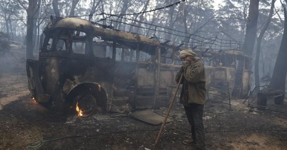 17.out.2013 - Sean Butler, morador de região atingida por incêndio florestal, fica ao lado de seu ônibus, de 1958, que foi destruído pelo fogo na cidade histórica de Newnes Junction, no norte do Estado de Lithgow, na Austrália, nesta quinta-feira (17)