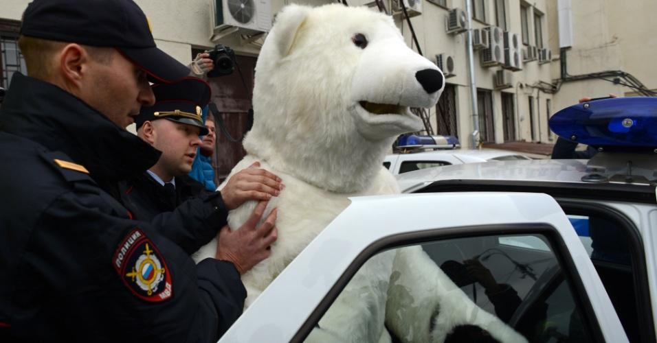 """18.out.2013 - Policiais russos detêm um homem fantasiado de urso polar após conflito com ativistas do Greenpeace em Moscou. A ONG organizou em várias cidades europeias um ato de apoio aos """"30 do Ártico"""", tripulantes do quebra-gelo 'Arctic Sunrise' que são acusados de pirataria por manifesto contra uma plataforma de petróleo da gigante russa Gazprom no Ártico"""