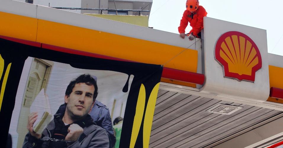 18.out.2013 - Ativistas do Greenpeace estendem faixa com o rosto do argentino Hernan Perez Orsi,  ativista do Greenpeace detido na Rússia desde setembro, em um posto de gasolina da Shell em Buenos Aires, na Argentina. Os tripulantes do quebra-gelo da ONG foram acusados de pirataria após um protesto contra uma plataforma de petróleo no Ártico russo