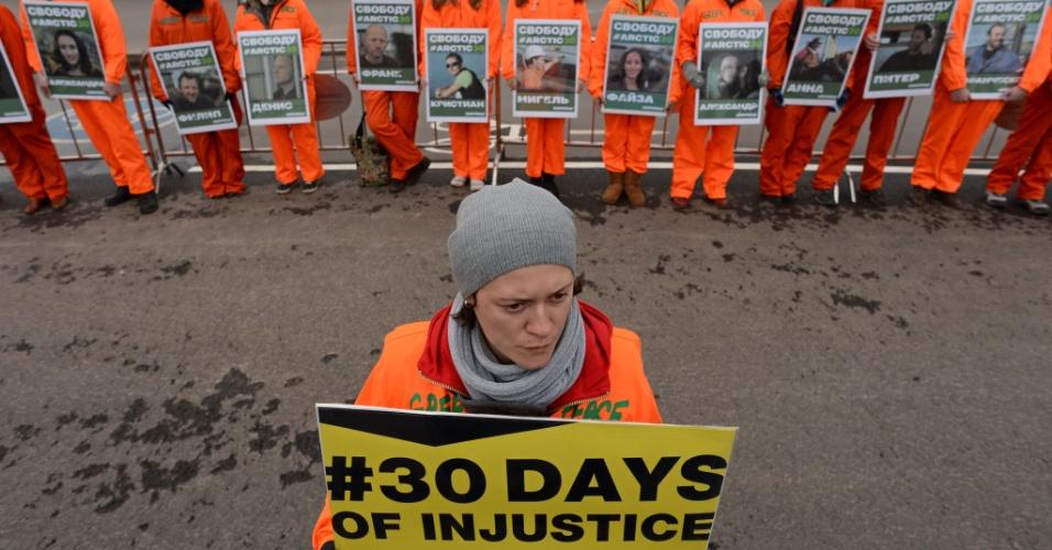 """18.out.2013 - Ativistas do Greenpeace mostram cartazes com os rostos dos """"30 do Ártico"""", tripulantes do quebra-gelo 'Arctic Sunrise' que foram detidos após um protesto contra uma plataforma de petróleo da gigante russa Gazprom no Ártico"""