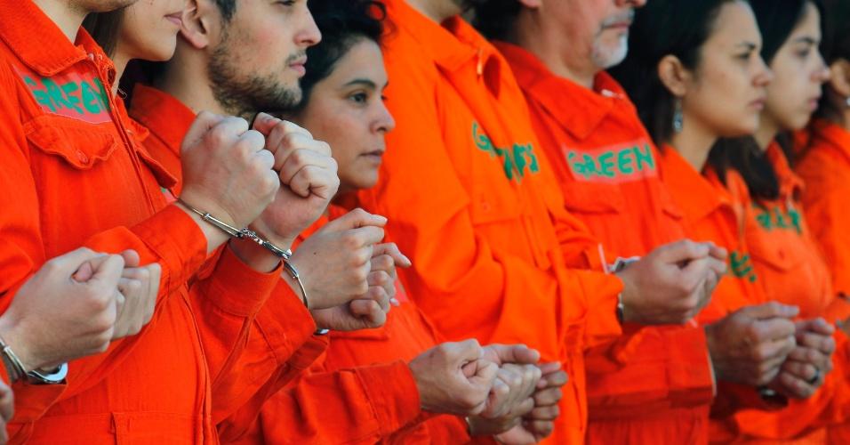 """18.out.2013 - Ativistas do Greenpeace se acorrentam em frente a um posto de gasolina da Shell em Buenos Aires, na Argentina, em ato de apoio aos """"30 do Ártico"""", que estão detidos na Rússia"""