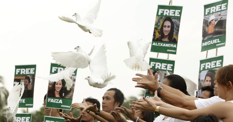 18.out.2013 - Membros do Greenpeace de Manila, nas Filipinas, soltam 30 pombas brancas em ato de apoio aos ativistas da ONG presos na Rússia desde setembro. Os 30 tripulantes do quebra-gelo da ONG foram acusados de pirataria após um protesto contra uma plataforma de petróleo no Ártico russo