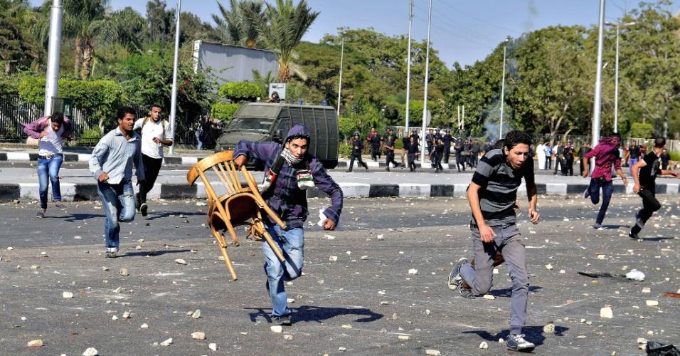 20.out.2013 - Estudantes da universidade de Al-Azhar correm de bombas de gás lacrimogêneo disparadas pelas Forças de Segurança durante uma manifestação próxima ao  campus, no Cairo, Egito. Os estudantes protestaram contra a destituição do presidente Mohammed Mursi, e pedindo a demissão do grão-imã Ahmed al-Tayeb, principal autoridade sunita do Egito. As forças de segurança e os estudantes entraram em confronto depois que os jovens tentaram marchar até a mesquita Rabaa Adawiya