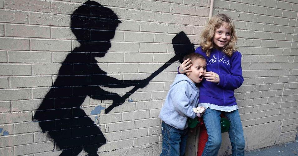 21.out.2013 - Crianças recebem uma martelada na cabeça? Nada disso! É apenas uma instalação do grafiteiro Banksy que está fazendo sucesso com os fotógrafos amadores e profissionais em Nova York