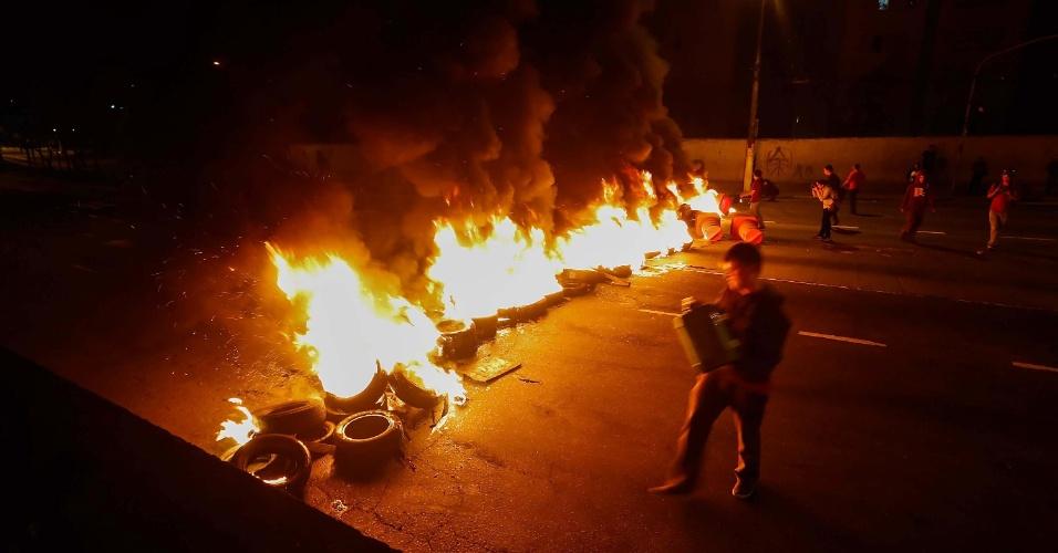 21.out.2013 - Grupo protesta nesta segunda-feira (21) contra corte de linhas de ônibus e pela duplicação da estrada M'Boi Mirim no Largo do Piraporinha, em São Paulo. Os manifestantes chegaram a interditar a avenida com barricadas de pneus com fogo