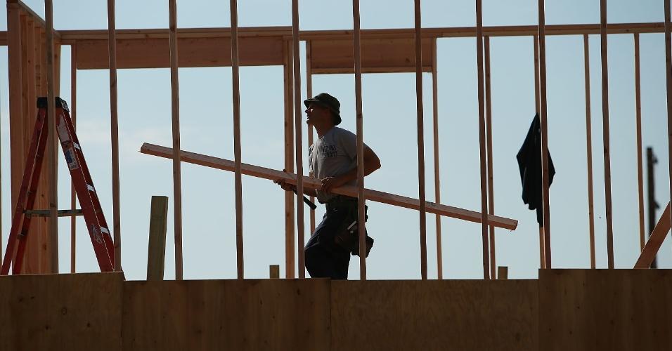 22.out.2013 - Um construtor ergue novas casas em uma área que foi gravemente devastada pelo furacão Sandy, onde novas moradias estão sendo construídas no bairro Breezy Point, no Queens, em Nova York, nesta terça-feira (22). Há um ano, o fenômeno climático atingia a região, que ainda se recupera dos efeitos do furacão. Moradores reconhecem os avanços conquistados ao logo do último ano, mas afirmam que os problemas ainda são evidentes. O furacão Sandy atingiu 24 Estados norte-americanos, da Flórida ao Maine, e trouxe prejuízos estimados em US$ 65 milhões para o país