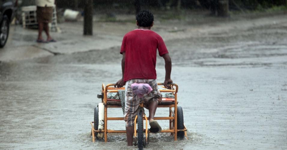 22.out.2013 - Um homem passa por uma rua inundada em Acapulco, no Estado mexicano de Guerrero, nesta terça-feira (22). Algumas pessoas que vivem em zonas de risco foram para abrigos, para se proteger dos possíveis ventos fortes do furacão Raymond, que se aproxima da costa mexicana