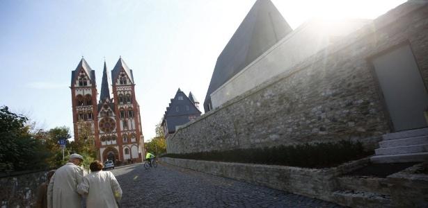 Casal que caminha em direção à catedral de Limburgo passa ao lado da casa do bispo Tebartz-van Elst