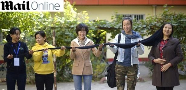 Amigas seguram o cabelo de três metros de comprimento de Ni Linmei, 57 anos: tesoura vai atacar