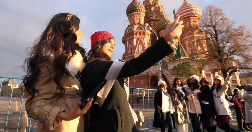 26.out.2013 - Lucia Aldana Roldan (e), Miss Colômbia, e Cynthia Duque (de gorro vermelho), Miss México, tiram foto juntas em frente à Catedral de São Basílio em Moscou, na Rússia. No dia 9 de novembro, a capital da Rússia sediará o Miss Universo 2013