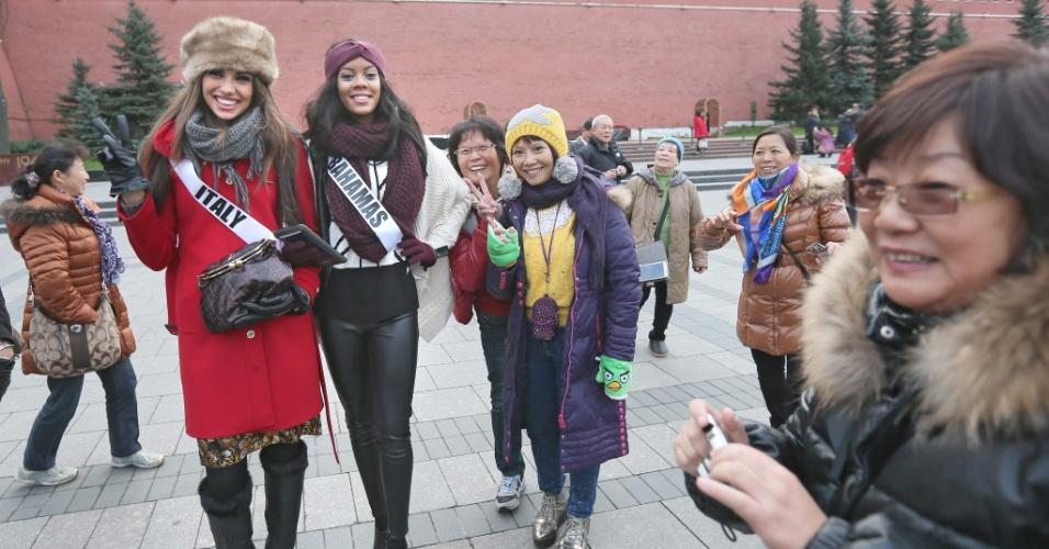 26.out.2013 - Luna Voce (e), Miss Itália, e Lexi Wilson (d), Miss Bahamas, posam para fotos com turistas orientais nas imediações do Kremlin, em Moscou (Rússia)