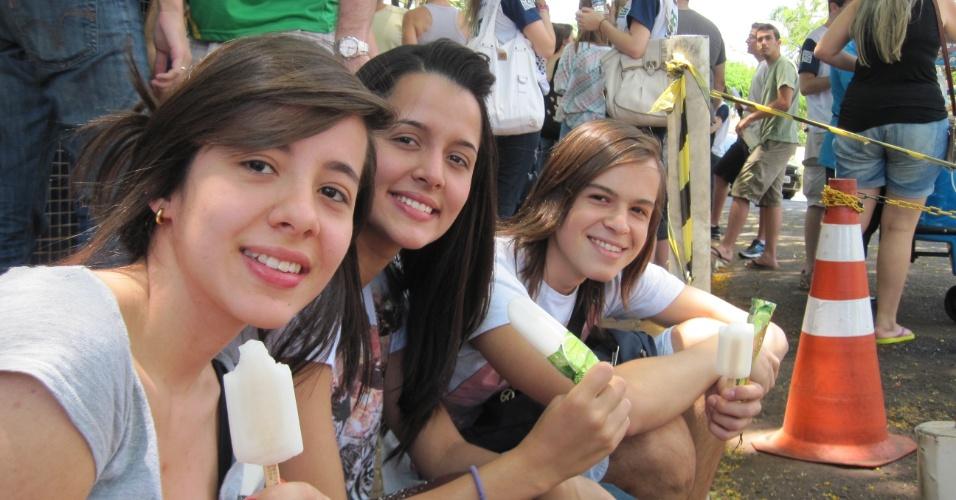 27.out.2013 - As irmãs Nadine, 17, e Natália Ramalho, 19, saboreiam um picolé de limão, com o amigo Pedro Leite, sob a sombra de árvores em frente à Unaerp, local de prova do Enem em Ribeirão Preto (SP)