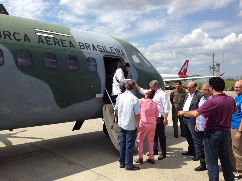 26.out.2013 - O ministro da Saúde, Alexandre Padilha, ajuda médica a descer de avião da FAB na Base Aérea de Guarulhos, onde os 276 profissionais do programa Mais Médicos que vão atuar em São Paulo chegaram neste sábado