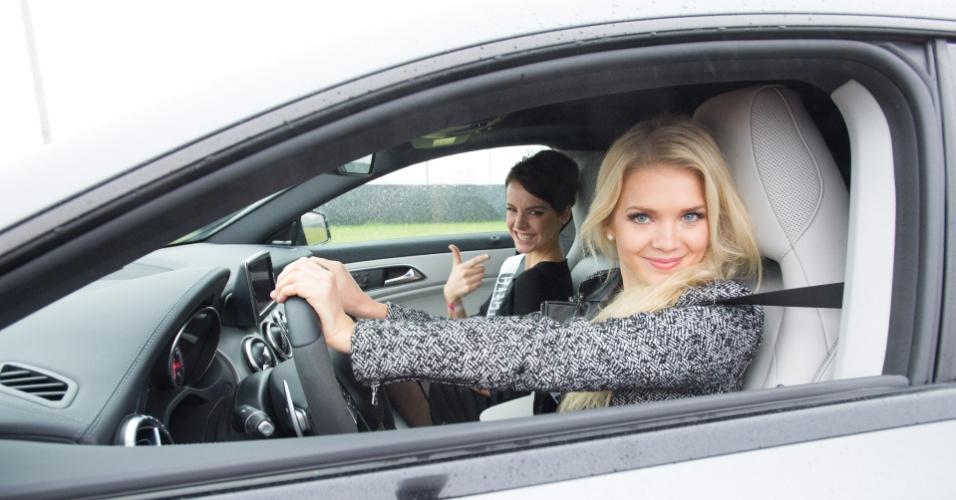 28.out.2013 - Lotta Hintsa, Miss Universo Finlândia; e Gabriela Kratochvilova, Miss Universo República Tcheca, se prepara para testar carro da Mercedes em pista de corrida de Moscou. O Miss Universo 2013 acontece no dia 9 de novembro e tem mais de 80 candidatas