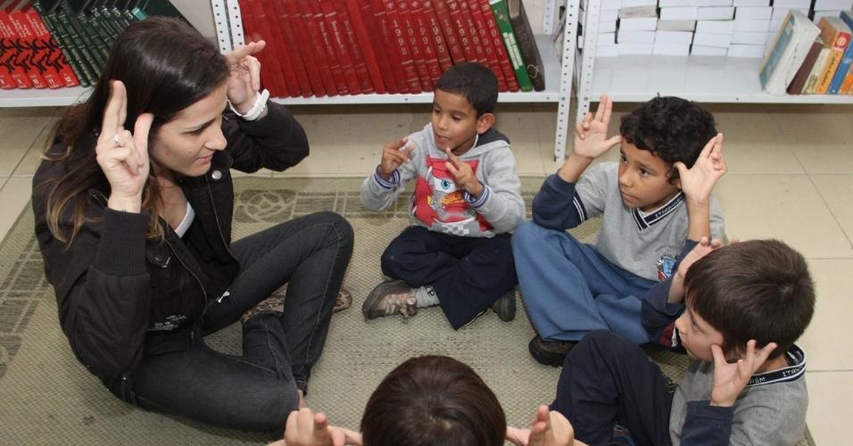 """A funcionária Daniele Cristina de Ponte é deficiente auditiva e conversa com os alunos por linguagem de sinais. As crianças pedem para ir ao banheiro e tomar água apenas usando os sinais que aprenderam no projeto """"Leitura por todos os sentidos"""", que tem o objetivo de ensinar braile e libras para os alunos da Escola Municipal Professora Silvia Regina Schiavon Marasca, em Itanhaém (a 114 km de São Paulo)"""